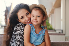 Beautiful happy mother hugging her joying smiling daughter indoor background royalty free stock photography