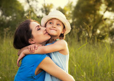 Beautiful happy mother hugging and kissing her grimacing fun dau Royalty Free Stock Image
