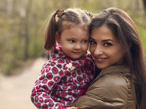 Beautiful happy mother and kid girl cuddling outdoors Stock Images