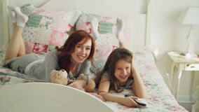 Beautiful happy mother with little daughter watching cartoon movie on TV and laughing while lying on bed at home in the. Beautiful young mother with little stock footage