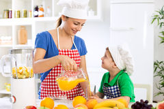 Beautiful happy mother pour orange juice to her child boy Royalty Free Stock Photos