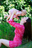 Beautiful happy mother throws child daughter up Royalty Free Stock Photography
