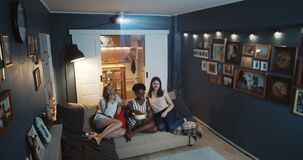 Beautiful happy multiethnic women friends laugh watching comedy TV show at home on big screen with projector slow motion