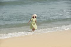 Beautiful happy multiracial Asian girl in vintage dresses walking. Beautiful happy multiracial Asian girl in vintage dresses relax and walking on the beach royalty free stock image