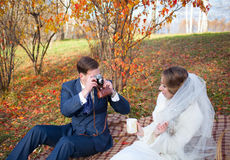 Beautiful happy newly married couple sitting on plaid in park, g Stock Photo