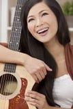 Beautiful Happy Oriental Woman Smiling & Guitar Stock Photo