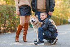 Happy beautiful family walking with dog in the park. Animal concept. Beautiful happy people having fun with doggie in the park outdoors. Happy family with puppy Royalty Free Stock Photo