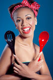 Beautiful happy pinup style housewife with kitchen. Utensils, studio shot royalty free stock photography