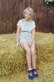 Beautiful happy preteen girl dressed in short bib overalls sitting on a hay in the village. Country style. Beautiful happy preteen girl 9-11 year old dressed in Royalty Free Stock Images