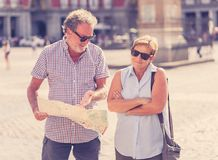 Happy retired senior tourist Couple Standing Taking Selfie in a European city. Beautiful happy retired tourist taking a selfie in Plaza Mayor Madrid Spain. In Stock Photos