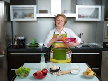 Beautiful and happy senior woman cooking at her kitchen Royalty Free Stock Photography