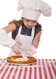 Beautiful happy seven year old girl in chef uniform with shortca Royalty Free Stock Photography