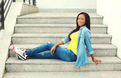 Beautiful happy smiling african woman wearing jeans clothes sitting Royalty Free Stock Photography