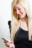Beautiful happy smiling blond young woman reading message on mobile Royalty Free Stock Photo