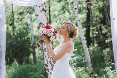 Beautiful happy and smiling bride in wedding dress standing with a bouquet of pions in hands. Stock Images