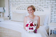 Beautiful happy and smiling bride in wedding dress standing with a bouquet of pions in hands. Royalty Free Stock Photo