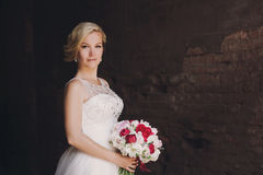 Beautiful happy and smiling bride in wedding dress standing with a bouquet of pions in hands. Stock Photography