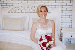 Beautiful happy and smiling bride in wedding dress standing with a bouquet of pions in hands. Royalty Free Stock Image