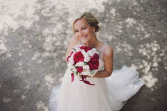 Beautiful happy and smiling bride in wedding dress standing with a bouquet of pions in hands. Stock Image