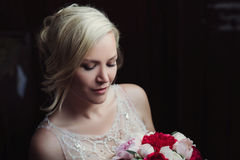 Beautiful happy and smiling bride in wedding dress standing with a bouquet of pions in hands. Stock Photos