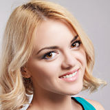 Beautiful happy smiling girl with blond hair, posing in studio. Royalty Free Stock Photography