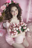Beautiful happy smiling girl with curly hair, teen with flowers. Tulips in hands over pink holiday party background Royalty Free Stock Photo