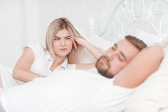 Sensual young couple together in bed. Happy couple in bedroom  on a white background. A beautiful happy smiling girl lies beside husband and looks like men with Royalty Free Stock Photos