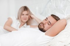 Sensual young couple together in bed. Happy couple in bedroom  on a white background. A beautiful happy smiling girl lies beside husband and looks like men with Royalty Free Stock Image