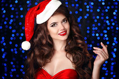 Beautiful happy smiling girl in santa hat with red lips, hand ho Stock Photo