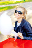 Beautiful happy smiling girl in sunglasses eating cotton candy at a table in the Park on a Sunny day Royalty Free Stock Photo