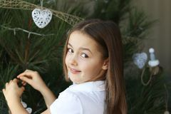 Beautiful happy smiling little girl decorating Christmas tree with white decorations royalty free stock photography