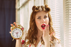Beautiful happy smiling pinup woman showing alarm clock Royalty Free Stock Photo
