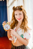 Beautiful happy smiling pinup woman showing alarm Stock Images