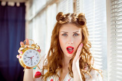 Beautiful happy smiling pinup woman showing alarm Stock Image