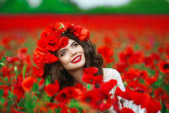 Beautiful happy smiling teen girl portrait with red flowers on h Stock Photos