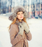Beautiful happy smiling woman wearing a coat and hat over snow in winter Royalty Free Stock Images
