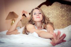 Beautiful happy smiling young blond woman in bed with stretching looking up at camera portrait Royalty Free Stock Image