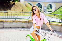 Beautiful happy smiling young woman on a bicycle Royalty Free Stock Images