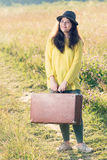Beautiful happy smiling young woman with brown vintage suitcase and black hat in the field road.  Royalty Free Stock Image