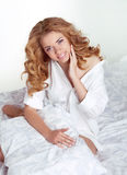 Beautiful happy smiling young woman with curly hair in bed at ho Stock Photography