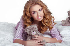 Beautiful happy smiling young woman  with teddy bear in bed at h Royalty Free Stock Images
