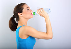 Beautiful happy sporty slim woman holding and drinking water fro. M the bottle on blue background. Closeup portrait stock photography