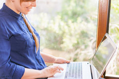 Beautiful happy student with a laptop sitting against bright window Royalty Free Stock Photos