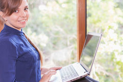 Beautiful happy student with a laptop sitting against bright window Royalty Free Stock Photo