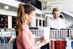 Beautiful happy students studying and flirting in a library royalty free stock photos