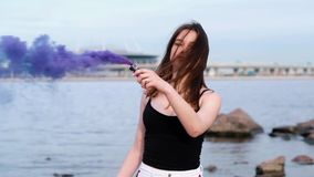Beautiful happy stylish sexy young girl at the seaside hold a light up colored smoke bombs. Slow motion stock video footage