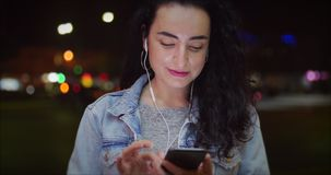 Beautiful Happy Stylish Young Pretty Girl in Jean Jacket with White Headphones and Long Dark Hair Messaging on the Smart stock footage