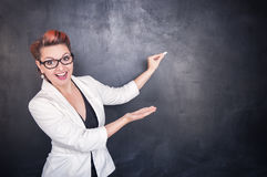 Beautiful happy teacher with piece of chalk. On blackboard background stock image
