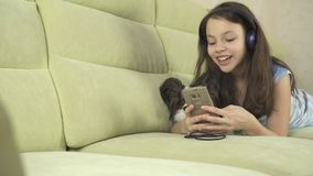 Beautiful teen girl in headphones singing karaoke songs in smartphone with dog. Beautiful happy teen girl in headphones singing karaoke songs in smartphone with Royalty Free Stock Images