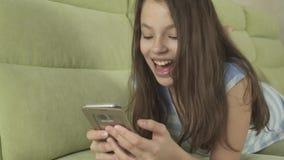 Beautiful teenage girl having fun communicating on smartphone stock footage video. Beautiful happy teenage girl having fun communicating on smartphone stock stock video footage